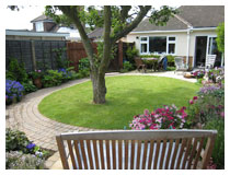 Oval lawn with curved path, patio laid in sandstone, borders and apple tree, seen from sitting-area.  Garden design and landscape gardening in Bedfordshire.