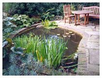 Pond, bog garden and york stone and brick patio in a corner of a country garden.
