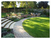 Patio, lawn, path, and steps to upper garden.  Planting includes roses, anemones and grasses.