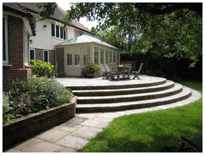 A large raised patio designed to give easy access from kitchen, dining room and conservatory and plenty of room for outdoor dining and leisure activities.  Sweeping steps provide easy access to the lawn.  A rear garden design in Hertfordshire.